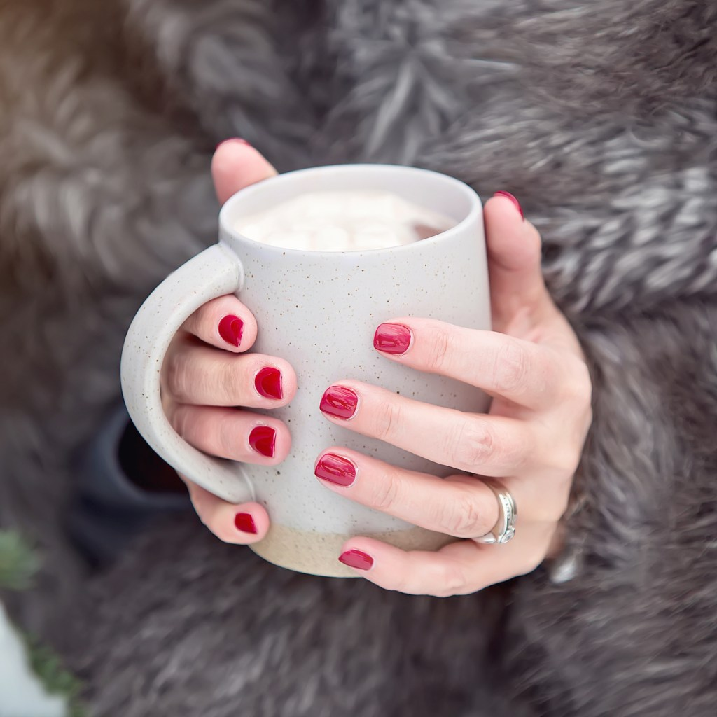 woman with red nails holding coffee cup. fur jacket. 10 easyways you can give back to your community
