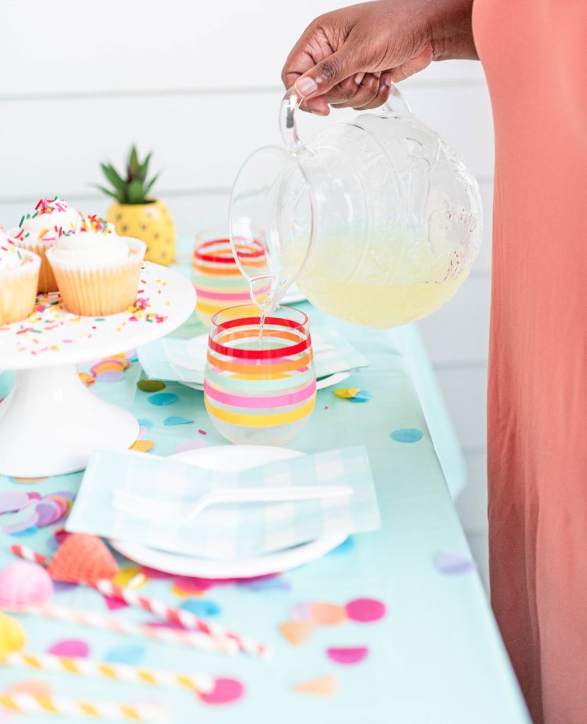 woman pouring lemonade into colourful striped glass. party table set up. striped straws, napkins.