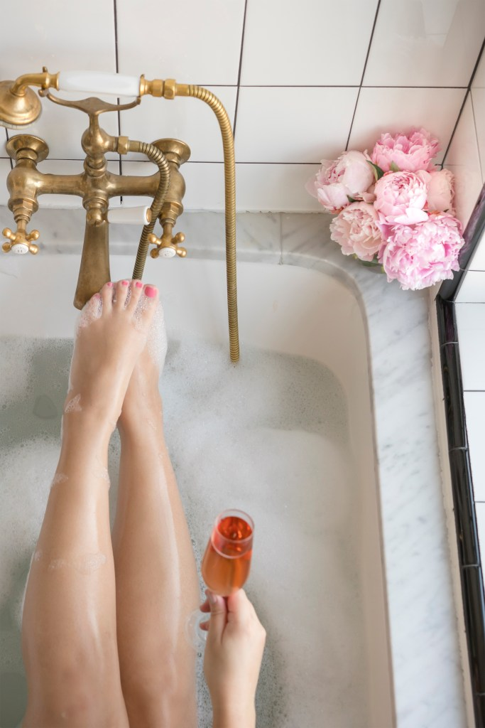 woman in bathtub enjoying bubble bath and a glass of  rosé. pink peonies in corner.