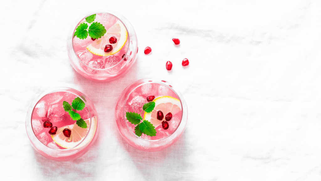pink cocktails with pomegranate seeds in stemless wine glasses on a marble countertop