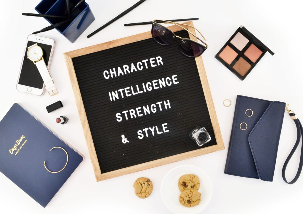 25 POSITIVE AFFIRMATIONS YOU NEED TO HEARletterboard that reads intelligence, strength & style. varius items surrounding the flatlay. navy themed.