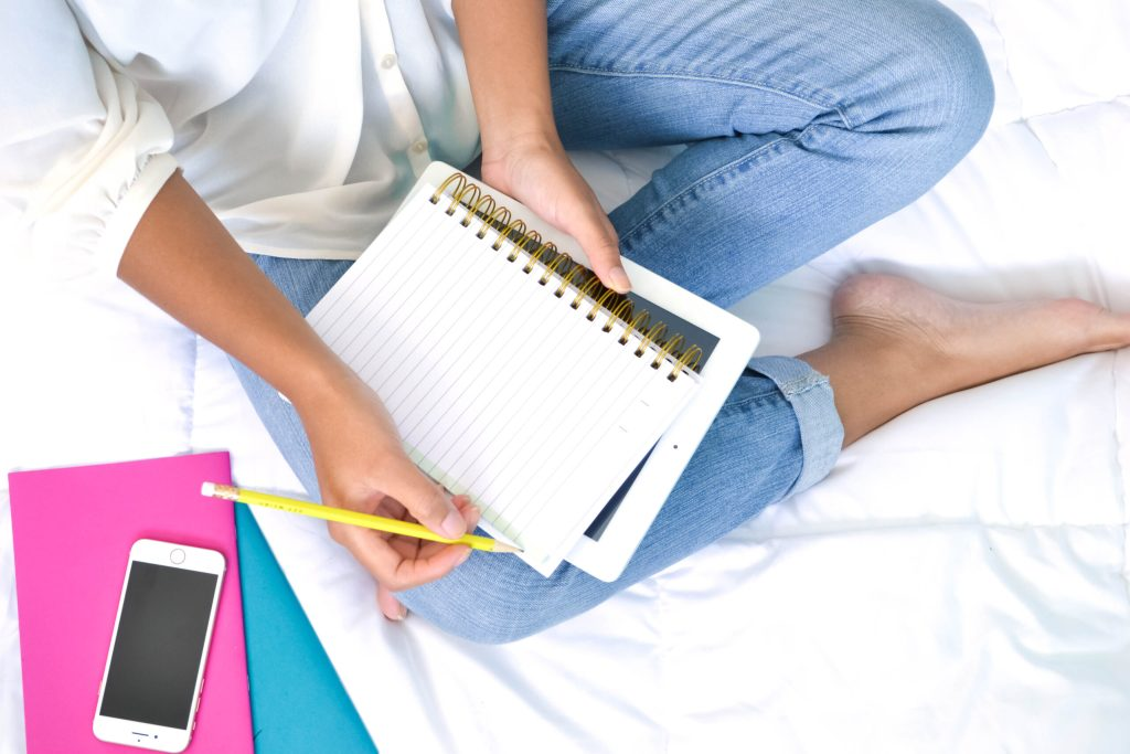 woman sitting on white bed sheet with white top and blue jeans. notebook, ipad and iphone beside her.