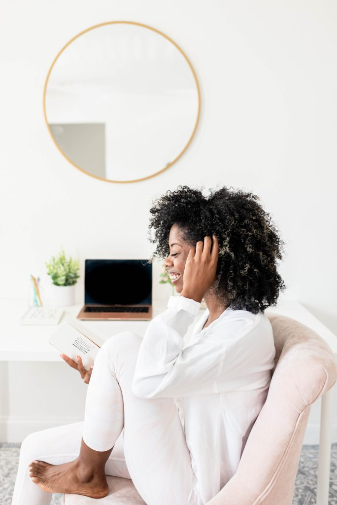 Black woman sitting on couch, touching hair, reading a book and smiling. background mirror and macbook.