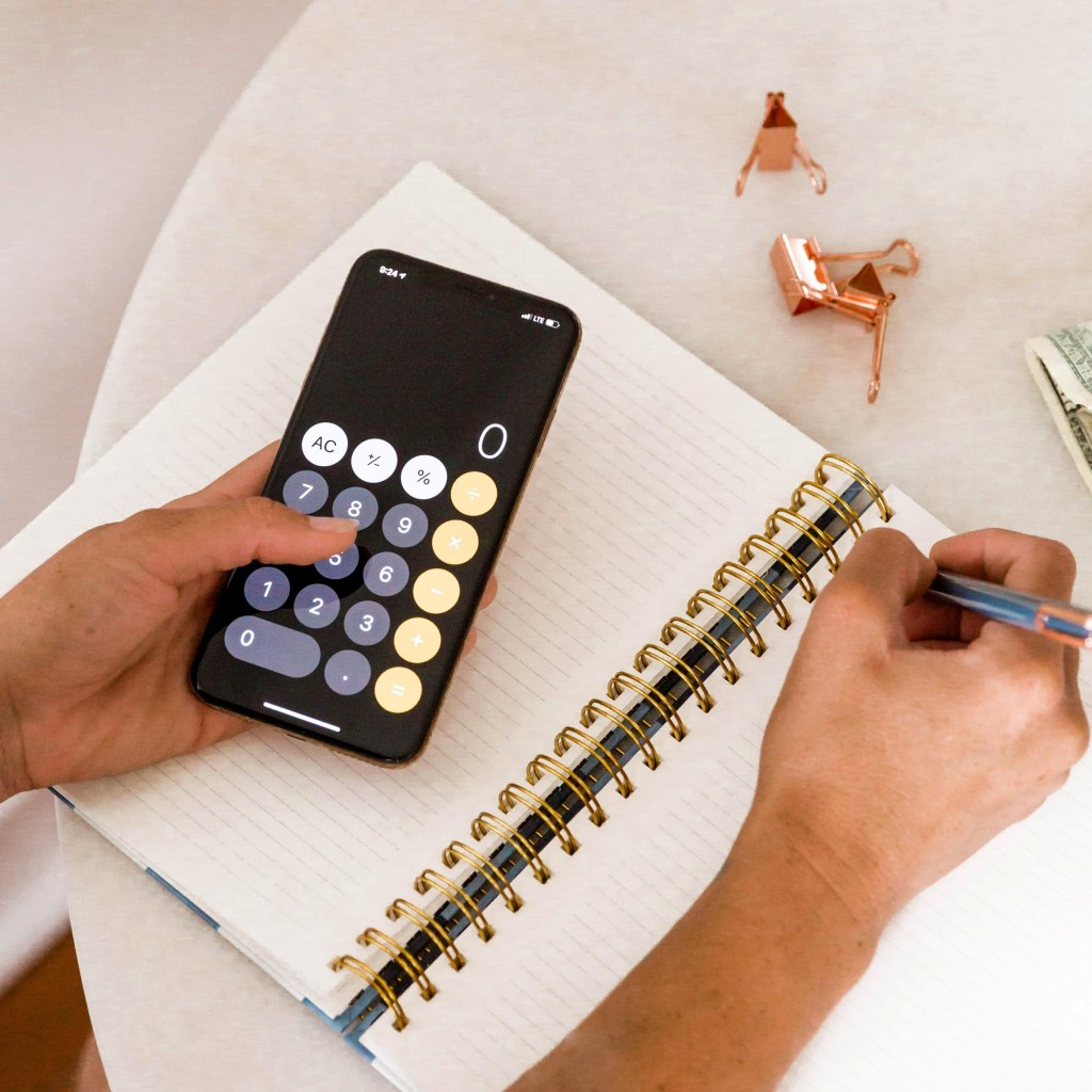 woman sitting with iphone calculator and notebook open.