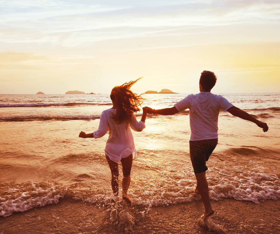 man and woman running into shoreline, on a date. 10 Adorable Date Ideas For the Ultimate Budget-Friendly Date Night
