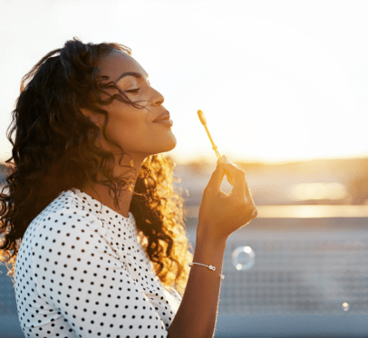 woman blowing bubbles into sunlight. 20 THINGS TO LEAVE BEHIND IN 2020: START THE NEW YEAR OFF WITH A LIGHTER MIND