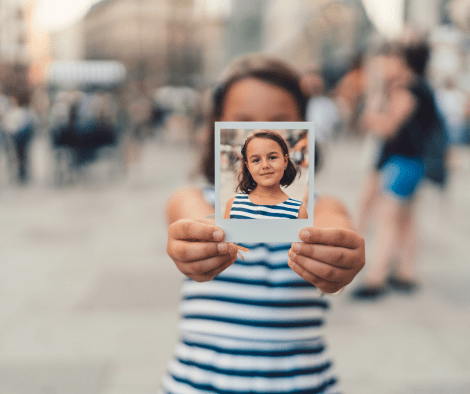 little girl holding out polaroid picture of herself. 50 Things to Be Grateful For