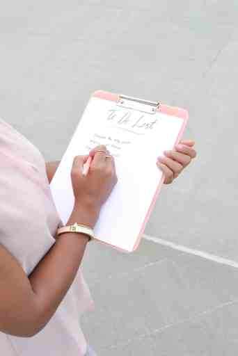 woman holding clip board that says to do list, wearing gold bracelet and pink shirt.