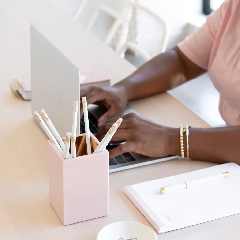 girl sitting at desk, typing on laptiop. pink pencil holder on desk.
