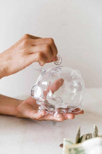 woman putting change into a clear glass piggy bank. paper bills on table.