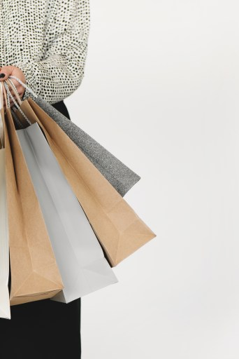 woman carrying grey and brown shopping bags. 10 POWERFUL WAYS YOU CAN SUPPORT LOCAL: AFFORDABLE TIPS THAT GO BEYOND SPENDING MONEY