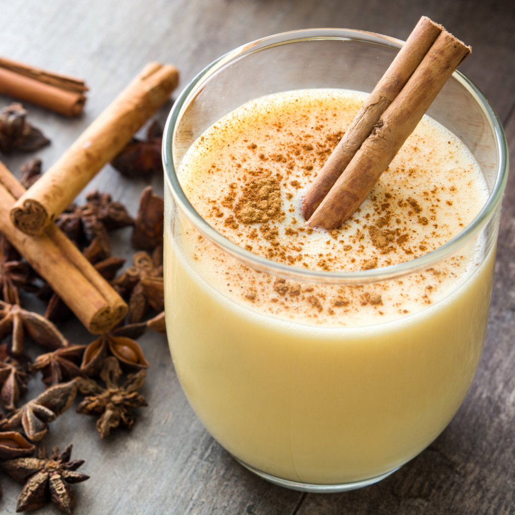 eggnog with cinnamon sticks and cloves
