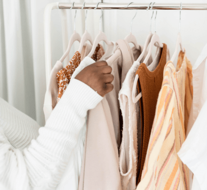 woman organizing brown, orange and white clothing on a rack. HOW TO DECLUTTER YOUR LIFE AND IMPROVE YOUR ENVIRONMENT: UNFRIEND, THROW OUT, & DELETE