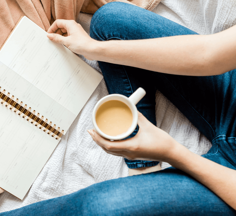 woman holding notebook and cup of coffee, wearing jeans and sitting on the bed