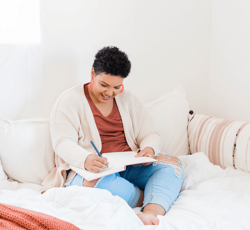 woman sitting on bed writing in notebook.
