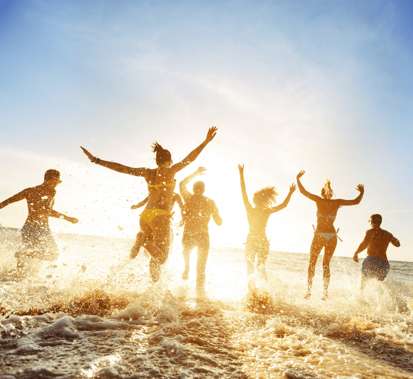 men and women running into shallow water at beach