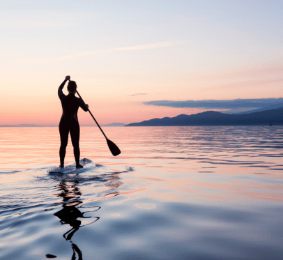 IN YOUR TWENTIES: 87 IDEAS TO CREATE THE ULTIMATE SUMMER BUCKET LIST. woman paddle boarding at sunset
