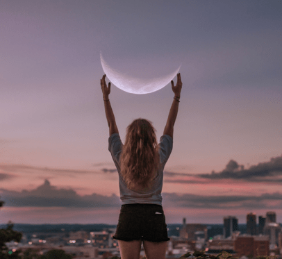 love herself. a woman reaching for the crescent moon.