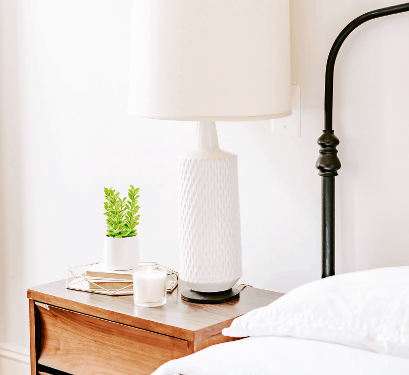bedside table with green plant and white lamp. Black metal bedframe, mattress and bedding