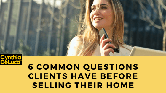 A real estate agent smiling and thinking about the common questions clients have before selling their home.