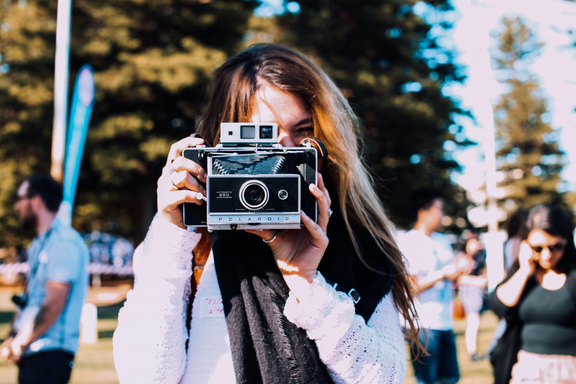 young woman taking photo on retro camera in crowded park