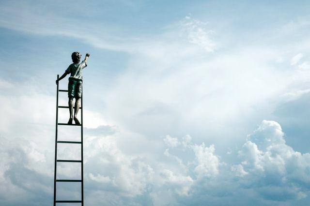 はしごをかけて空に手を伸ばす子ども