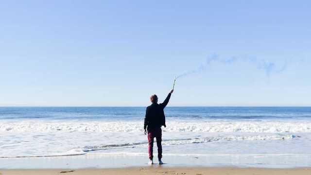 砂浜で発煙筒を上げる男性