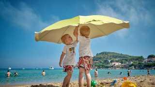 砂浜でパラソルをさす幼い兄弟