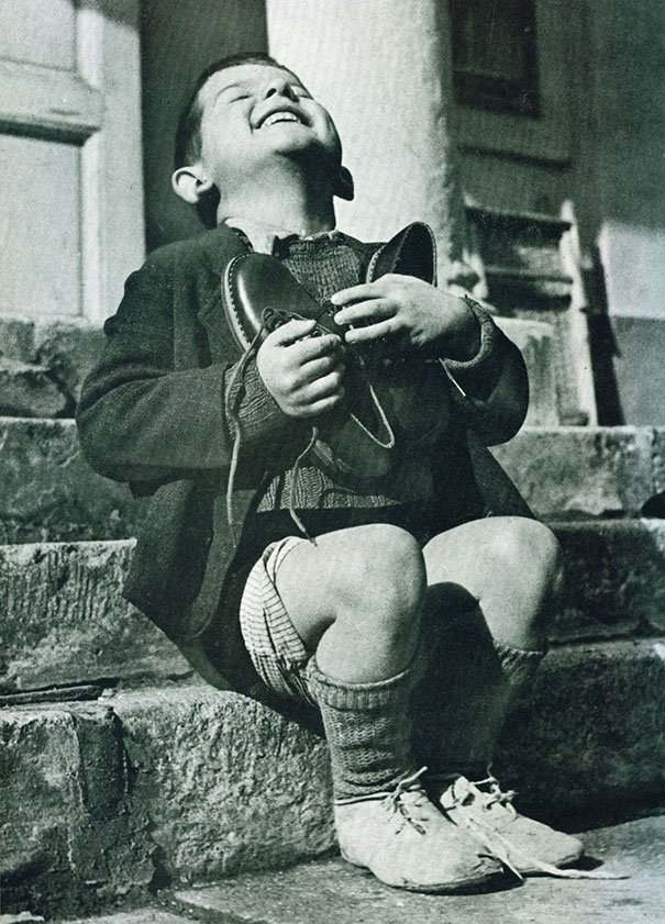 """New Shoes"" by Gerald Waller, Austria 1946  Six year-old Werfel, living in an orphanage in Austria, hugs a new pair of shoes given to him by the American Red Cross."