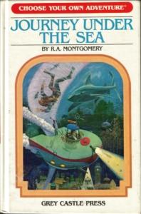 """Okładka gry paragrafowej """"Journey under the sea"""" z serii """"Choose your own adventure"""". Przedstawia łódź podwodną płynącą nad zatopionym miastem, tonącego człowieka i płynące w jego stronę dwa rekiny."""