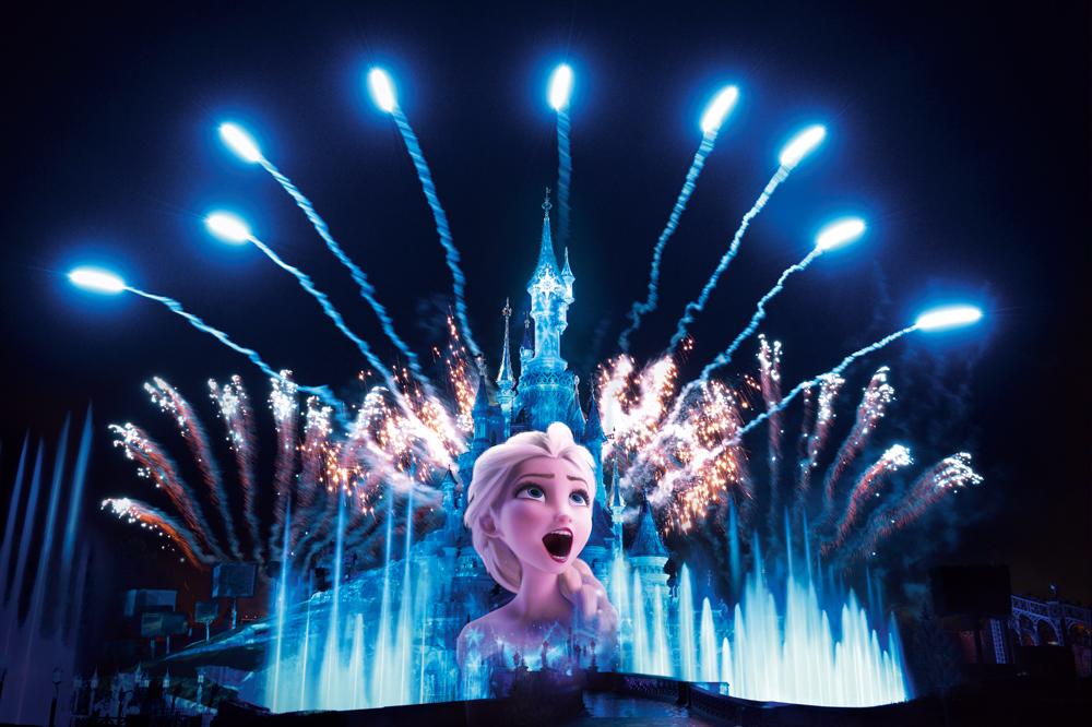Elsa, één van de twee hoofdpersonen uit Frozen, wordt geprojecteerd op het kasteel van Doornroosje omgeven door fonteinen en vuurwerk