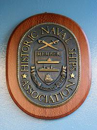 """Памятная табличка о вступлении крейсера 1-го ранга  """"Аврора"""" во всемирную ассоциацию исторических кораблей.  Вручена 26 мая 2004 года."""