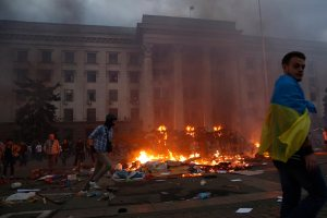 A protester wrapped in a Ukrainian flag walks past a burning tent camp and a fire in the trade union building in Odessa