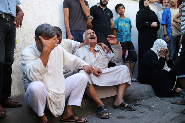 The grandfather of the Al-Rifi children cries outside a hospital morgue in Gaza City