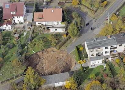 An aerial view shows a landslide under a residential ...