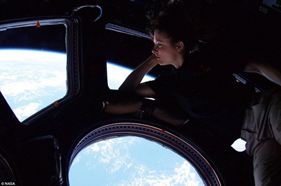 Astronaut Tracy Caldwell Dyson looks down at ...
