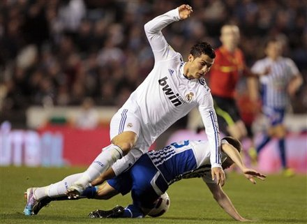 Real Madrid's Cristiano Ronaldo From Portugal, Left, Falls As He Vies For The Ball With Deportivo La Coruna's Laureano