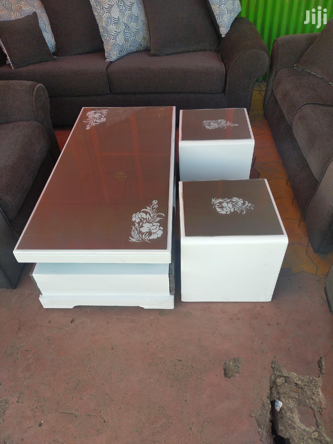 grey and white coffee table with glass top and two stools