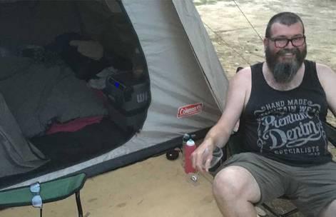 David sitting outside tent Bright