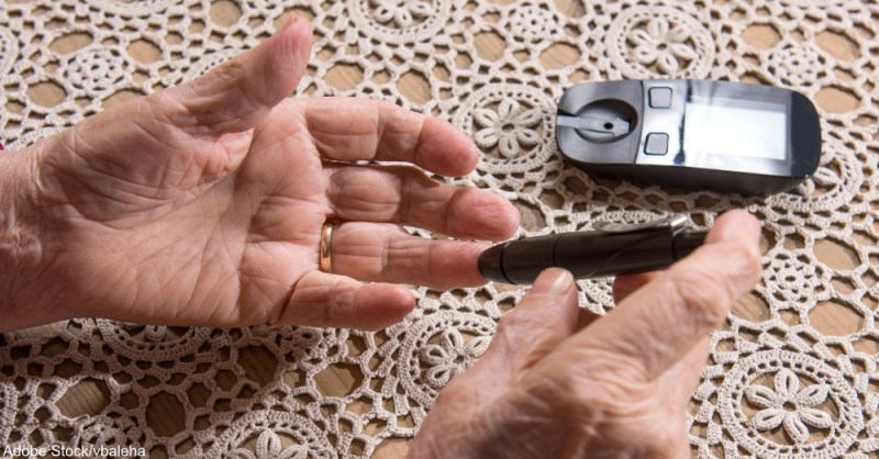 Old woman with glucometer checking blood sugar level