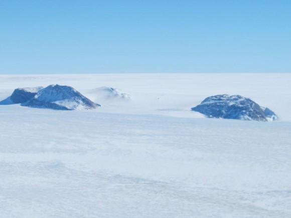 Nunataks en la porción occidental de la capa de hielo de Groenlandia se ve desde la NASA P-3B durante un estudio IceBridge del sudoeste de Groenlandia, el 8 de abril de 2013.  Nunataks son áreas de roca expuesta en una capa de hielo, tales como crestas o picos de montaña.  Estas formaciones de rocas irregulares a veces se utilizan como puntos de referencia en una capa de hielo.  Crédito: NASA / Jim Yungel.