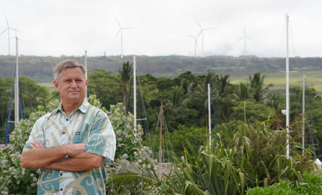 Senator Gil Riviere stands at Alii Park in Haleiwa with windmills above Waimea Bay at the top of the photograph.