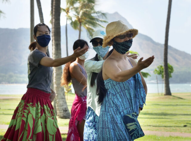 A group of women dance hula together under the direction of Kumu hula Mahealani Kalikolau 'olenakalani at the Magic Island Park in Honolulu, Thursday, July 9, 2020. (Ronen Zilberman photo Civil Beat)