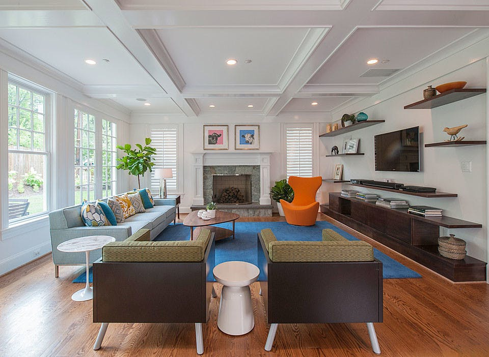 full view of a colorful great room, featuring a beautiful Modern orange chair.