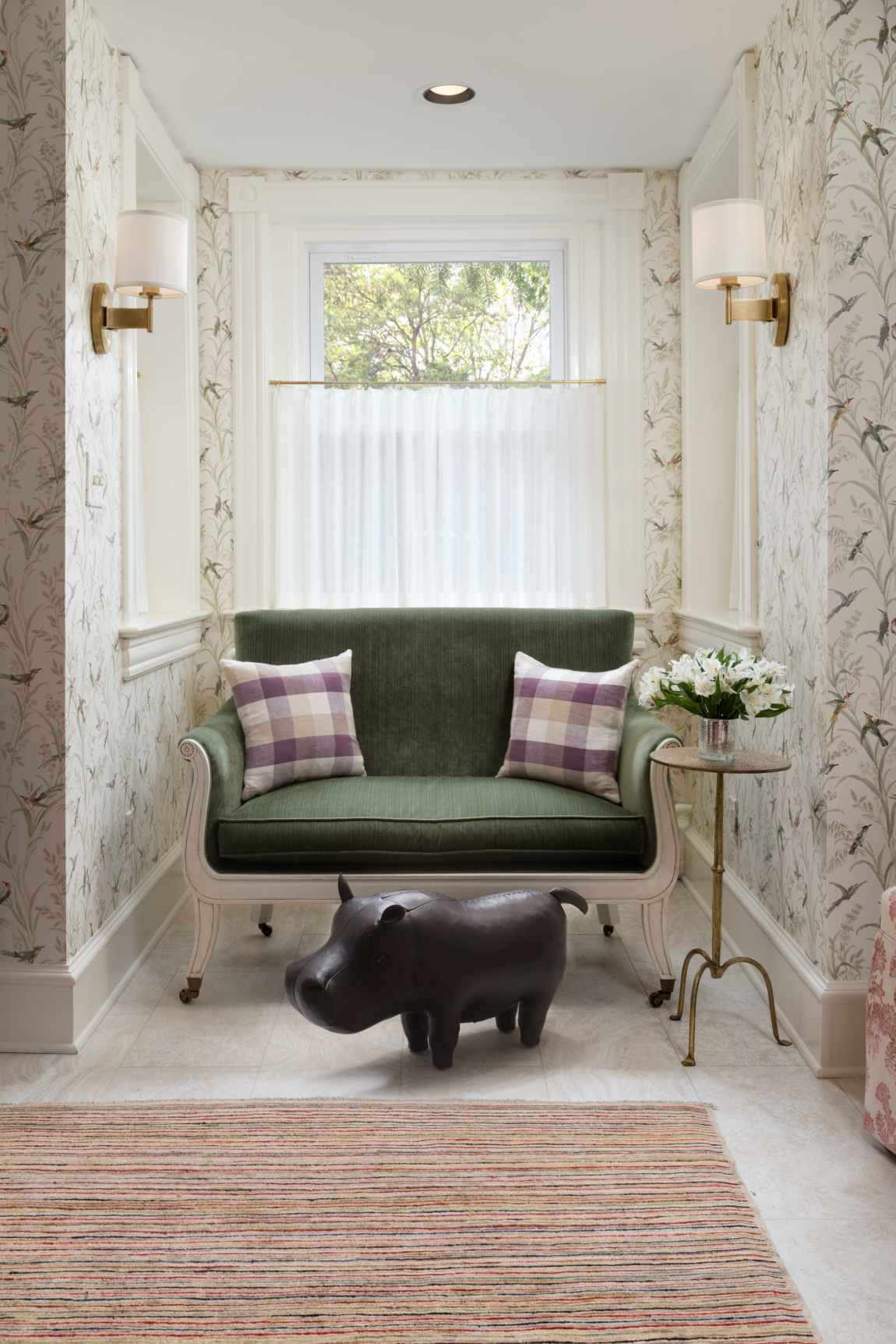 Reading nook with interesting side table and hippo sculpture.