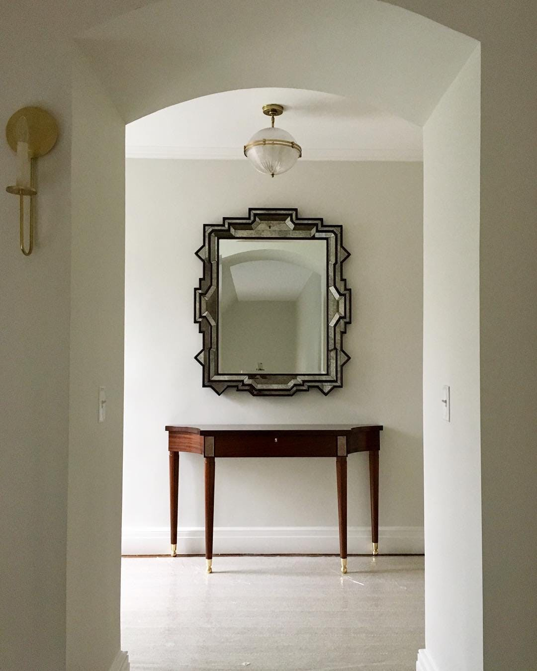 Longview of traditional foyer with a beautiful, foxed mirror and traditional console table