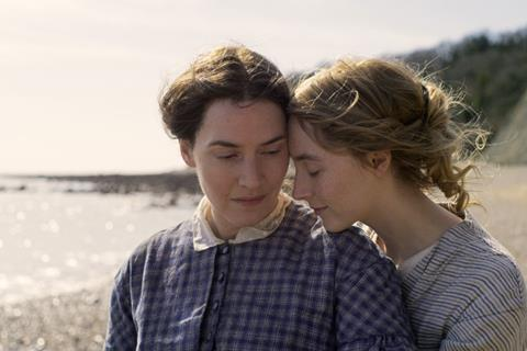 Kate Winslet and Saoirse Ronan sitting on a beach in Ammonite, a queer movie coming 2020
