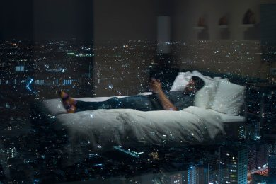 A man lying on a hotel bed with city lights all around through the windows