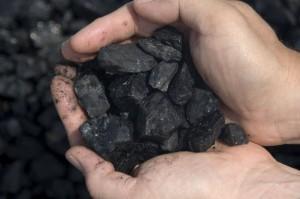 hands holding coal