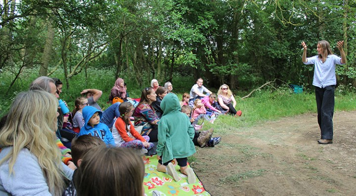 Photograph of middle school group listening to a story in the woods.